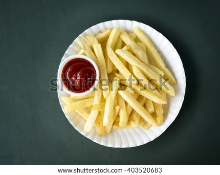 Close up French fries potatoes with ketchup on white dish. - stock photo