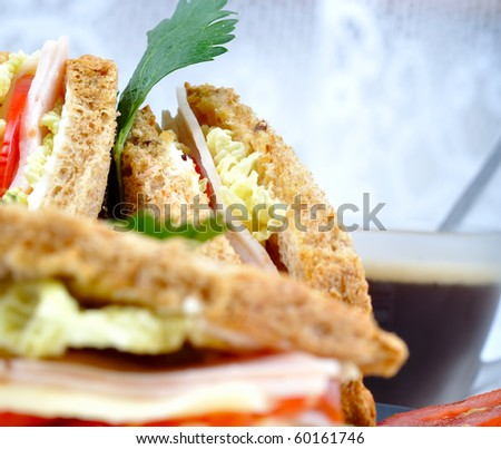 close up fresh and delicious classic club sandwich over a black glass dish with coffee and vegetable - stock photo