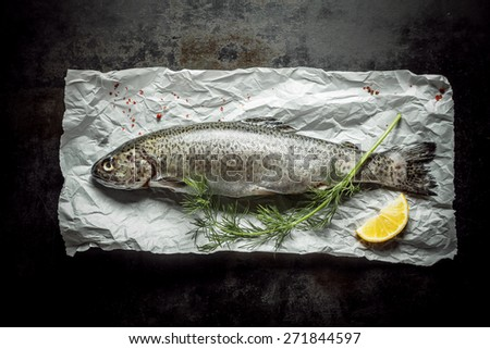 Close up Fresh Fish Meat on Top of a Paper with Green Herb and a Slice of a Lemon, Placed on Top of a Rustic Table, Captured in High Angle View. - stock photo