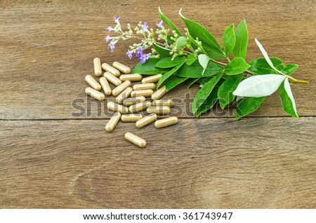 Close up fresh flower Vitex trifolia Linn or Indian Privet with green leaf  is herb in Thailand and drug pill on wooden background - stock photo