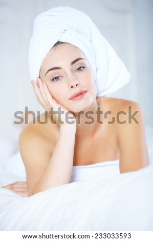 Close up Fresh From the Shower Pretty Young Woman Lying Down on White Bed  Wrapping her Hair with White Towel  with One Hand on the Face While Looking at the Camera. - stock photo
