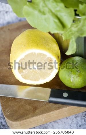 close up fresh lemon cut half with knife on cutting board - stock photo