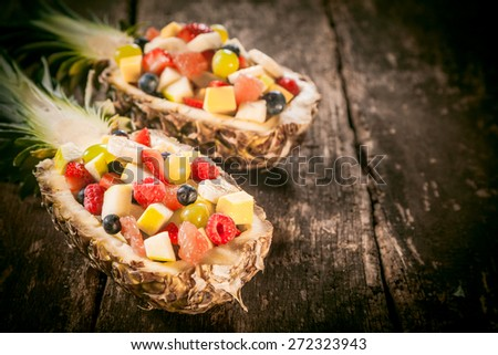Close up Fresh Tropical Fruit Salads in Pineapple Boats on Top of a Rustic Wooden Table. - stock photo