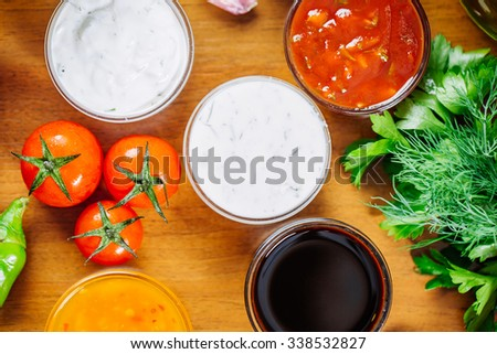 Close up Fresh Various Spices and Sauces on the wood kitchen Table - stock photo