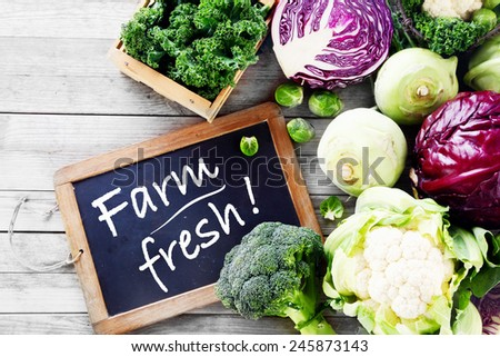 Close up Fresh Vegetable for Salad from the Farm on Wooden Table with Black Chalkboard Signage - stock photo
