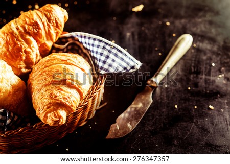 Close up Freshly Baked Buttery Croissant Bread on a Basket and a Cutting Knife on Top of the Table - stock photo