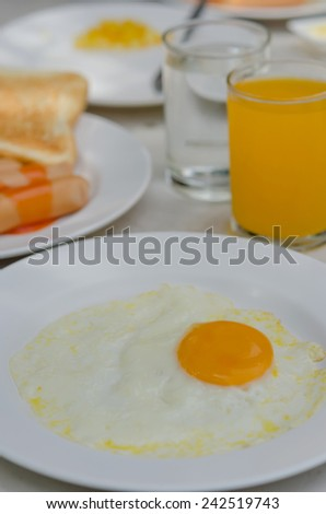 close up fried eggs on a white plate with orange juice for breakfast - stock photo