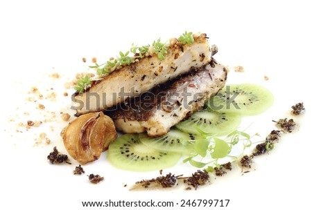 Close up fried fish fillet served with kiwi slices - stock photo