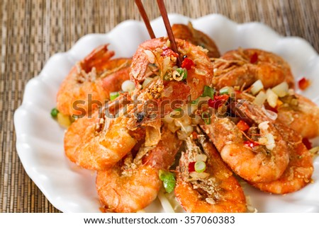 Close up front view of a fried bread coated shrimp, selective focus on single piece in chopsticks, with fresh garnishes.  - stock photo