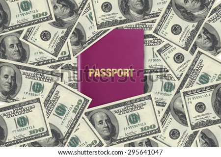 Close up front view of a passport, among one hundred dollar banknotes as background. - stock photo