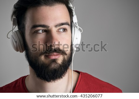 Close up front view portrait of young man with headphones looking away with copyspace  - stock photo