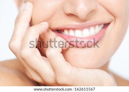 Close up frontal beauty section portrait view of a young woman natural smile with voluptuous pink lips leaning on her hand smiling with white teeth, classic beauty detail indoors. - stock photo