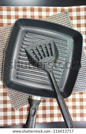 Close up frying pan and kitchen utensils on table. - stock photo