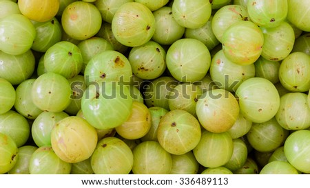 Close-up, full frame view group of fresh ripe Indian gooseberries in fruit stall at Little India Singapore. The dessert cultivars as luscious as the best apple, strawberry or grape. Gooseberry texture - stock photo