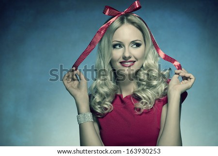 close-up funny portrait of cute blonde girl with xmas bow on her head like a gift, wearing red elegant dress and bright bracelet  - stock photo