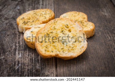 Close up garlic bread on old wood background - stock photo
