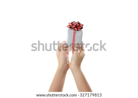 Close up gift box with red ribbon in kids hand isolate on white background. - stock photo