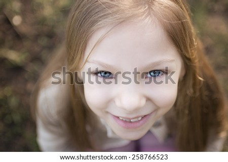 Close-up girl's face, photographed from above. With a smile on her face and beautiful blue eyes looking at the camera. - stock photo
