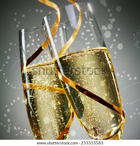 Close up Golden Wine on Flute Glasses with Gold Laces on Abstract Gray Background. A New Years Day Concept Design. - stock photo