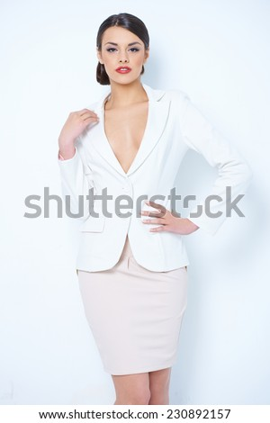 Close up Gorgeous Young Woman Wearing White and Light Pink Corporate Attire   Showing her Cleavage While Posing in Front of the Camera.Isolated on White Background. - stock photo