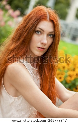 Close up Gorgeous Young Woman with Long Blond Hair, Posing at the Garden While Looking at Camera - stock photo