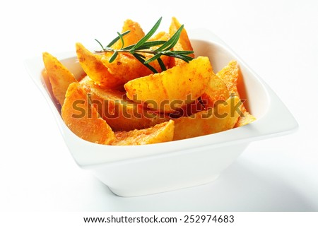 Close up Gourmet Golden Brown Fried Potatoes in White Bowl with Rosemary Herb on Top, Isolated on White. - stock photo