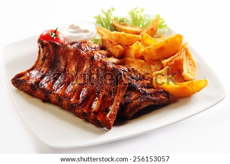Close up Gourmet Grilled Pork Rib and Fried Potato Wedges on White Plate with Sauce and Veggies, Isolated on White Background. - stock photo