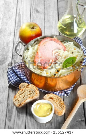 Close up Gourmet Healthy Recipe on Wooden Table with Smoked Pork Chop on Top of Vegetable Salad and Bread and Mustard Sauce on the Side. - stock photo