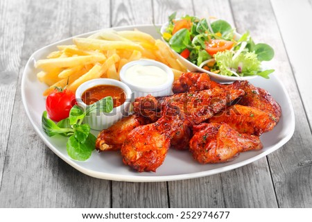 Close up Gourmet Main Dish for Dinner with Crispy Fried Chicken, French Fries and Veggies on White Plate. Served on Wooden Table. - stock photo