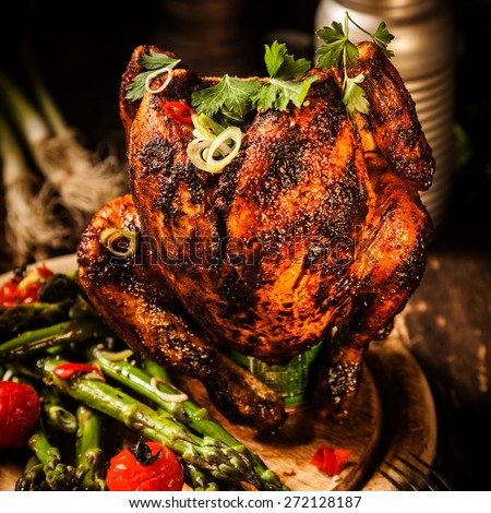 Close up Gourmet Roast Whole Beer Can Chicken With Asparagus, Cherry Tomatoes, Herb and Spices, Served on Top of a Wooden Table. - stock photo