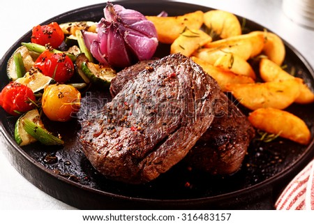 Close up Gourmet Tasty Pepper Crusted Beef Steak with Grilled Vegetables on a Cast Iron Skillet on Top of a Table. - stock photo