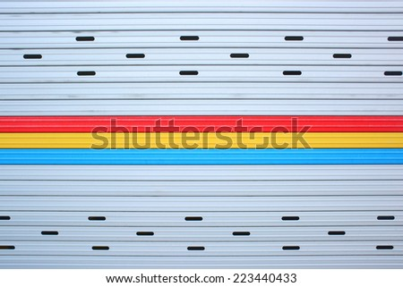 Close up gray, red, yellow, blue metal sheet slide door texture background. - stock photo