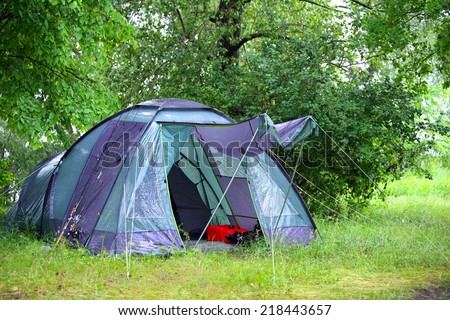 close-up green tourist tent in the woods under a tree in summer - stock photo