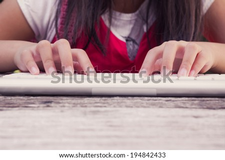 Close up gril hands typing on the keyboard  - stock photo