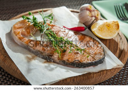 Close up grilling steak from fish, Salmon steak with grilled lemon and garlic decorated with herbs, rosemary and temyan on the wooden plate - stock photo