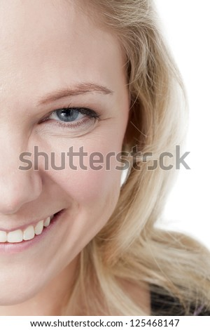 Close-up half face of a happy woman over the white background - stock photo