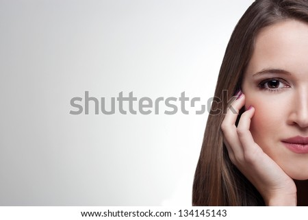 Close-up half face portrait of beautiful woman isolated on a light grey background - stock photo