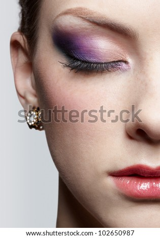 close-up half-face portrait of young beautiful woman with violet eye shadow closing eyes - stock photo