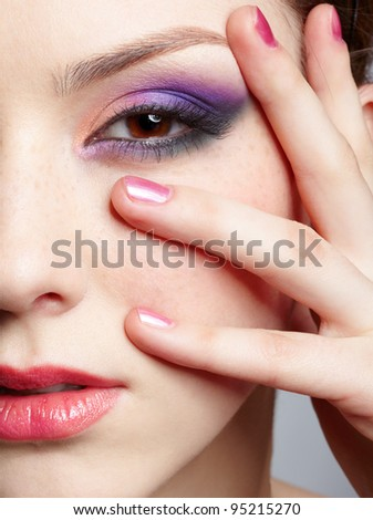 close-up half-face portrait of young beautiful woman with violet eye shadow touching her face with manicured hand - stock photo
