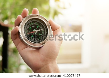 Close up Hand hold with compass on bright blurred background,vintage effect. - stock photo