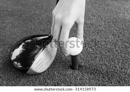 Close-up Hand holding golf ball and a golf wood on a driving range - stock photo