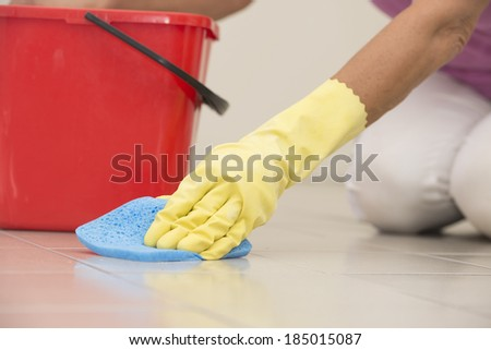Close up Hand in yellow rubber glove cleaning floor tiles with sponge, with woman, housewife in blurred background and copy space. - stock photo