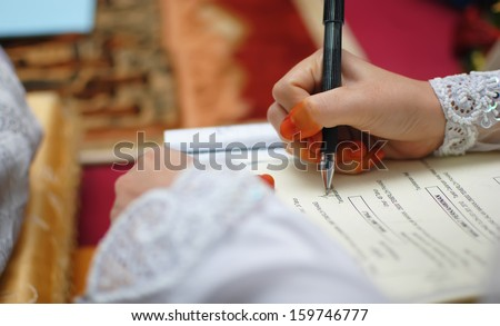 close up hand of a muslimah bride signing on the form of registration for muslim wedding. focusing on the hand with shallow depth of field - stock photo