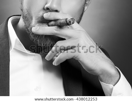 Close-up hand of bearded caucasian man smoking a cigar. Wearing grey suit and white shirt. Studio portrait on gradient black to grey background. Black and white - stock photo