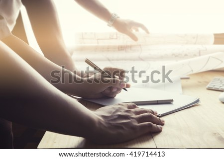 Close-up hand Of male Architect Drawing Blueprint on work space wooden table in offfice ,cross process and soft flare filter  - stock photo