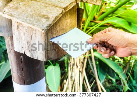 close-up, hand of man sent letter in post box, space for your text - stock photo