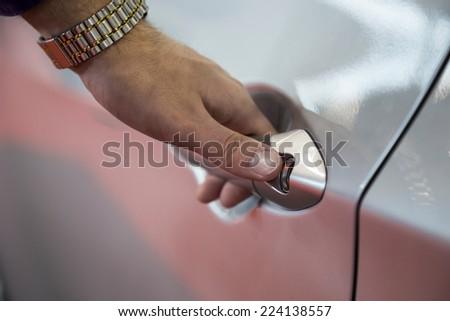 Close up hand opening a new, modern car door - stock photo