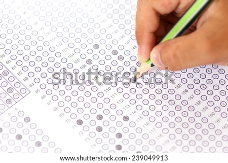 Close up hand with pencil on answer sheet - stock photo