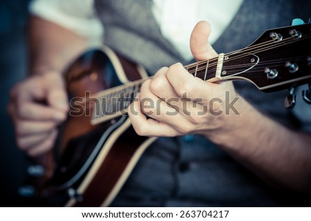 close up hands hipster man playing mandolin in the city - stock photo