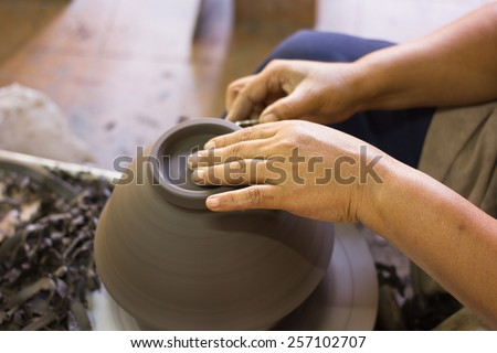 Close up hands of a potter, creating an earthen jar for Ceramic export to Japan - stock photo